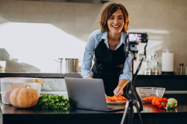 Videoblogger der jungen frau, der an der küche kocht und filmt