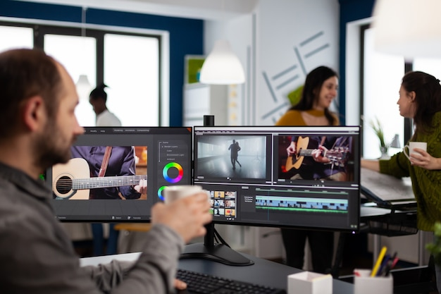 Videofilmer, der filmprojekt beim kaffeetrinken mit postproduktionssoftware bearbeitet, die in einem digitalen multimediaunternehmen mit zwei monitoren arbeitet