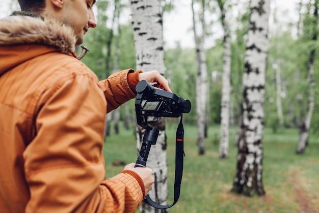 Videofilmer filmt den frühlingswald. mann, der steadicam und kamera verwendet, um gesamtlänge zu machen. videodreh