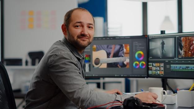 Videofilmer lächelt in die kamera und arbeitet an der bearbeitung von videomaterial und audio-app am computer, die in mo...