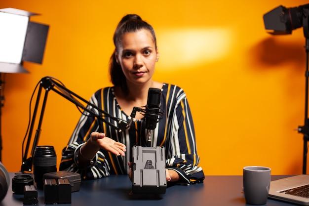 Videofilmer zeigt wiederaufladbaren akku an kamera mit li-ion