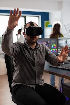 Videograf, der ein vr-headset trägt und das bearbeitungsprojekt in der postproduktionssoftware gestikuliert, sitzt im studiobüro