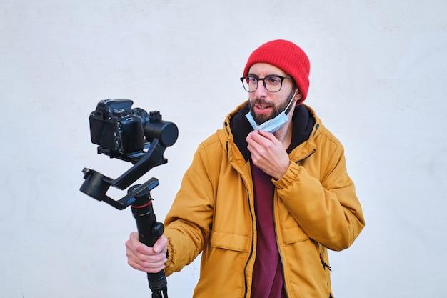 Videograf, der sich mit einer dslr-kamera auf einem motorisierten kardanring mit schützender gesichtsmaske aufzeichnet