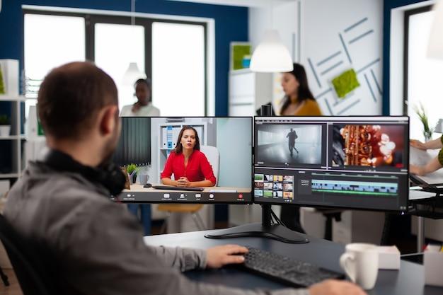 Videograf in web-online-konferenz mit projektmanager bei videoanruf-bearbeitung der kundenarbeit, erhalt von feedback zu kommerziellen filmen mit postproduktionssoftware auf zwei monitoren im start-up-büro