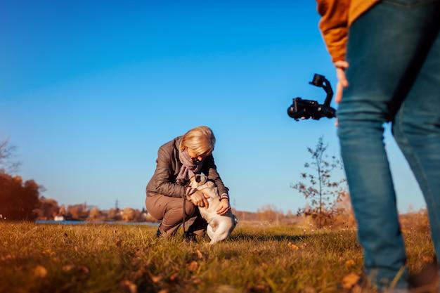 Videographer, der frau mit hund im herbstpark filmt mann, der steadicam und kamera verwendet, um gesamtlänge zu machen