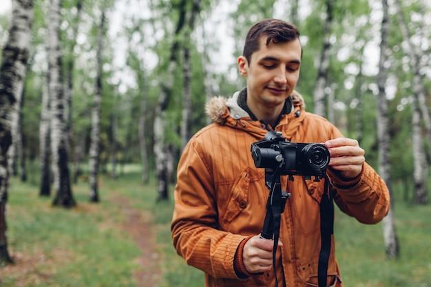 Videographer, der frühlingswald filmt mann, der steadicam und kamera verwendet, um gesamtlänge zu machen