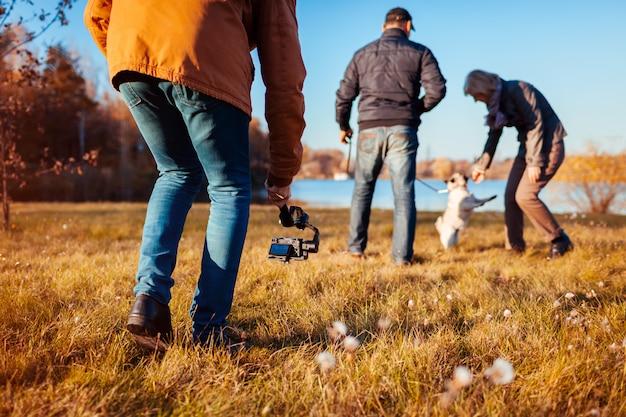 Videographer, der paare mit hund im herbstpark filmt mann, der steadicam und kamera verwendet, um gesamtlänge zu machen