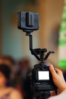Videographer, der video mit dslr-kamera aufnimmt. detail der professionellen kameraausrüstung. kameramann kamera einstellen