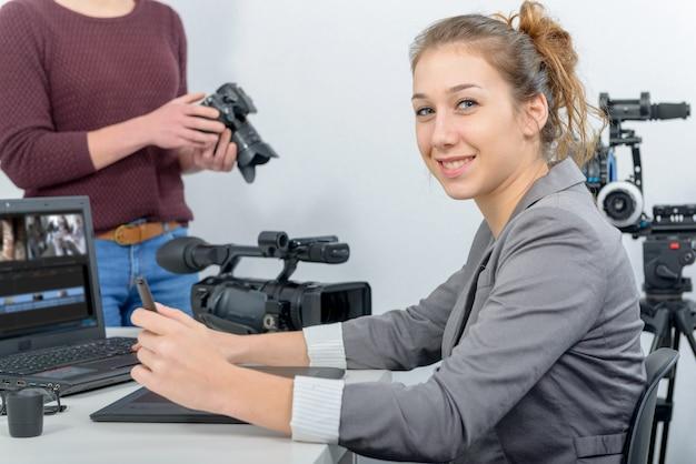 Videoherausgeber mit zwei jungen frauen, der mit laptop arbeitet