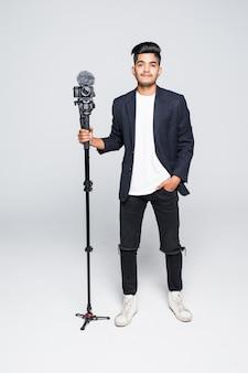 Videokamera-betreiber des jungen indischen mannes lokalisiert auf weißem hintergrund.