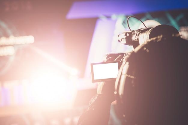 Videokamerabediener, der mit seiner ausrüstung im preiszeremoniethema kreativ arbeitet