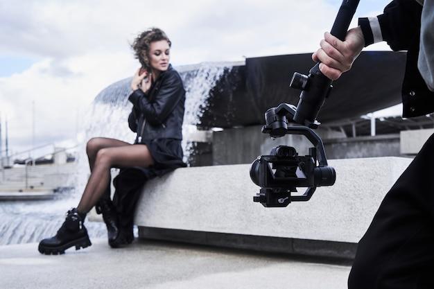 Videokameramann, der mit mode-modellmädchen im freien arbeitet