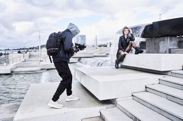 Videokameramann, der mit modemodellmädchen im freien arbeitet