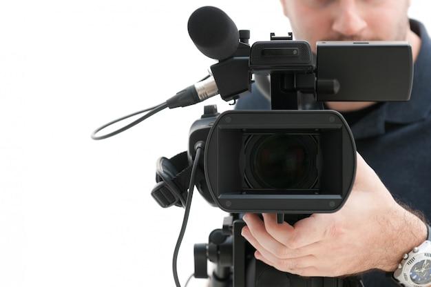 Videokameramann, der mit seiner professionellen ausrüstung arbeitet, lokalisiert auf weißem hintergrund