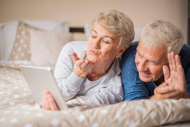Videokonferenz des fröhlichen älteren paares