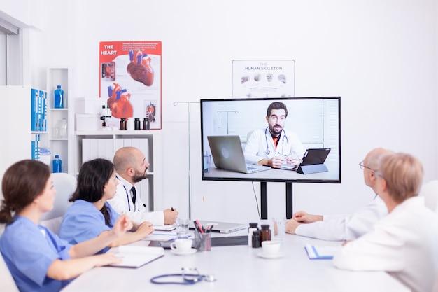 Videokonferenz des krankenhausteams mit facharzt. medizinpersonal, das das internet während des online-treffens mit dem therapeuten verwendet, um fachwissen zu erhalten