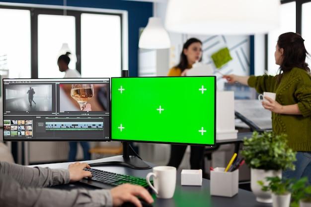 Videomacher, der filme mit postproduktionssoftware bearbeitet, die in der kreativagentur am pc mit grünem bildschirm, chroma-key, isolierter anzeige arbeitet