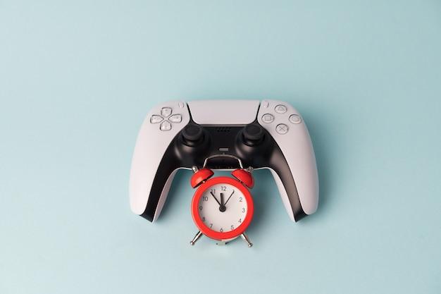 Videospielkonsolen-gamepad an der blauen wand mit rotem wecker. tim zum spielen. spielerproblem in abhängigkeit vom spiel.