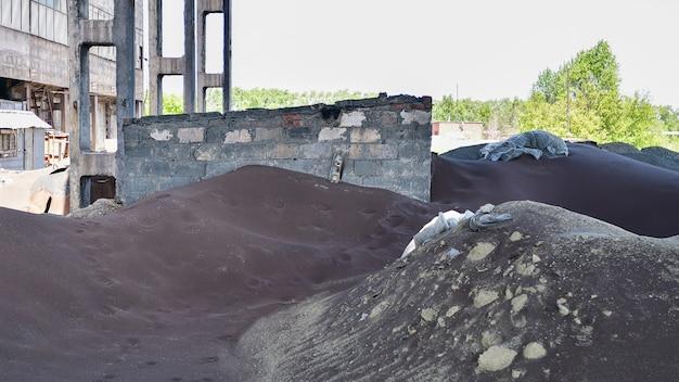Viel dunkle schlacke aus der eisen- und stahlindustrie in einer verlassenen fabrik.