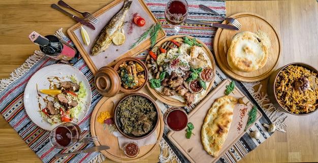 Viel essen auf dem holztisch. georgische küche. khinkali und georgische gerichte