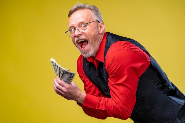 Viel geld in händen. dollar in händen. mann hält dollarstapel von dollarscheinen. menschliche emotionen und mimik. sehr aufgeregter mann mit viel geld.