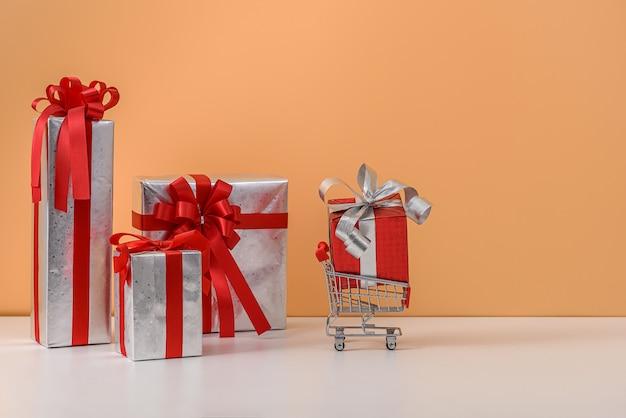 Viel geschenkbox mit rotem bandbogen und warenkorb oder laufkatze auf weißer tabelle und pastell