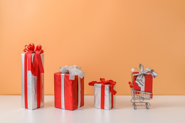 Viel geschenkbox mit rotem bandbogen und warenkorb oder laufkatze
