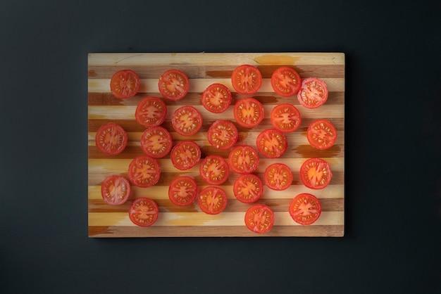 Viel geschnitten in halben frischen roten tomaten auf einem schnittbrett, vegeterian salatbestandteile
