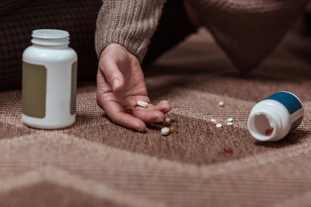 Viel medizin. nahaufnahme einer frau, die auf dem boden liegt und mit der einnahme von medikamenten selbstmord begeht