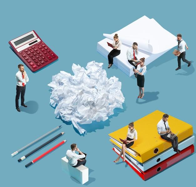 Viel papierkram. hohe betrachtungswinkel des kreativen modernen büros auf blauem hintergrund - große dinge und kleine arbeiter. büroarbeit, tägliche aufgabe, typische probleme und lifestyle-konzept. collage.