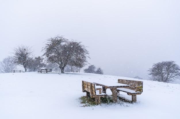 Viel schnee auf dem picknickplatz neben der zuflucht des berges aizkorri in gipuzkoa. schneelandschaft im winter schneit