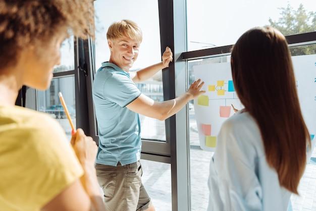Viel spaß bei der arbeit. positiv begeisterte junge kollegen, die im büro stehen und gemeinsam an dem projekt arbeiten