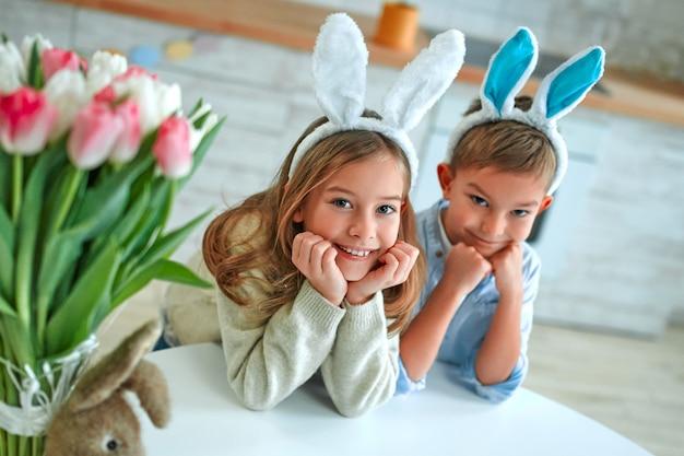 Viel spaß bei der ostereiersuche. kind junge und mädchen tragen hasenohren und sitzen am tisch mit ihren händen unter dem kinn. entzückende kinder feiern ostern zu hause.