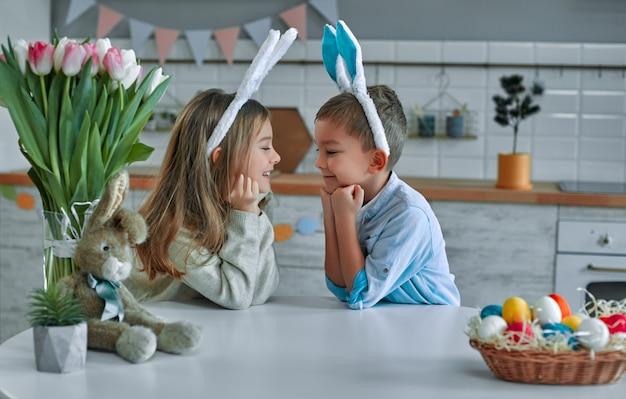 Viel spaß bei der ostereiersuche. kind junge und mädchen tragen hasenohren und sitzen am tisch mit ihren händen unter dem kinn und schauen sich an.
