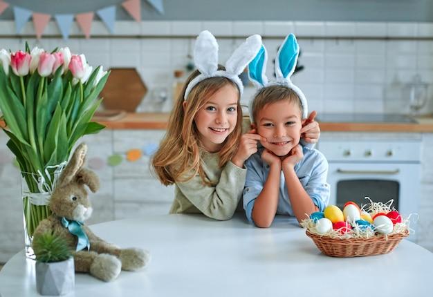 Viel spaß bei der ostereiersuche. kinderjunge und -mädchen, die hasenohren tragen und am tisch sitzen. entzückende kinder feiern ostern zu hause.