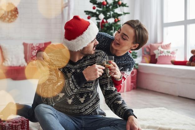 Viel spaß beim gespräch. zwei leute sitzen auf dem boden und feiern neujahr