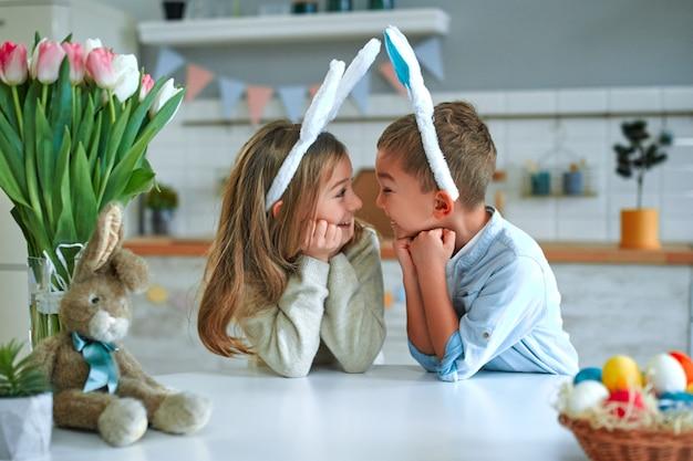 Viel spaß beim ostereiersuchen. kinderjunge und -mädchen, die hasenohren tragen und mit den händen unter dem kinn am tisch sitzen und sich ansehen.