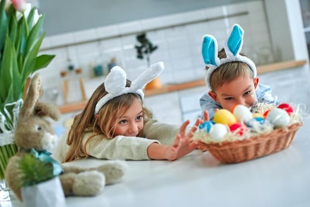 Viel spaß beim ostereiersuchen. kinderjungen und -mädchen, die hasenohren tragen und ihre hände mit eiern zum korb ziehen. entzückende kinder feiern ostern zu hause.