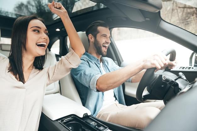Viel spaß beim reisen. schönes junges paar, das auf den beifahrersitzen sitzt und lacht, während ein gutaussehender mann auto fährt