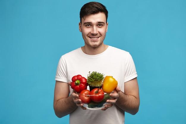 Viel spaß. glücklicher erfreuter attraktiver junger mann, der gesunden lebensstil und bio-rohkost wählt