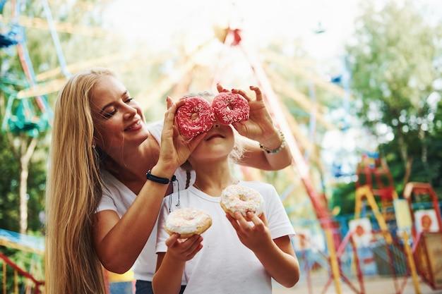 Viel spaß mit donuts. fröhliches kleines mädchen, ihre mutter, haben eine gute zeit im park zusammen in der nähe von attraktionen.
