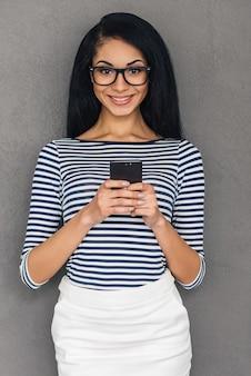 Viel spaß mit ihrem neuen handy. attraktive junge afrikanerin, die ein smartphone hält und mit einem lächeln in die kamera schaut, während sie vor grauem hintergrund steht