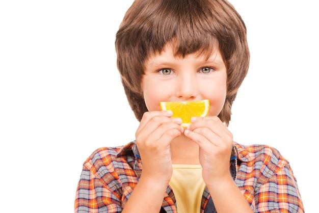 Viel spaß mit orange. fröhlicher kleiner junge, der den mund mit einem stück orange bedeckt, während er isoliert auf weiß