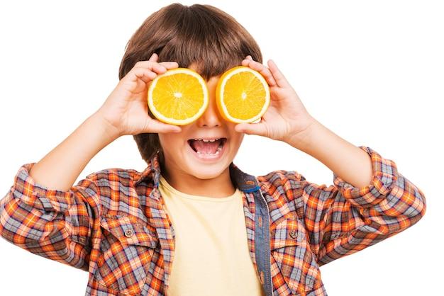 Viel spaß mit orange. fröhlicher kleiner junge, der die augen mit orangenstücken bedeckt und lächelt, während er auf weiß isoliert ist