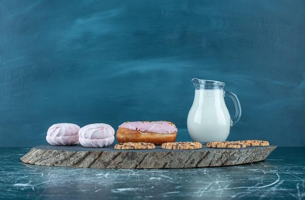 Viel süßes süßwaren mit milch auf einem dunklen brett. hochwertiges foto