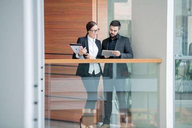 Vielbeschäftigte junge analysten, die digitale tablets verwenden, während sie online-informationen im bürokorridor untersuchen