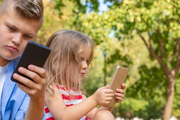 Vielbeschäftigte kinder, die auf ihre telefone schauen, sms schreiben und draußen sitzen