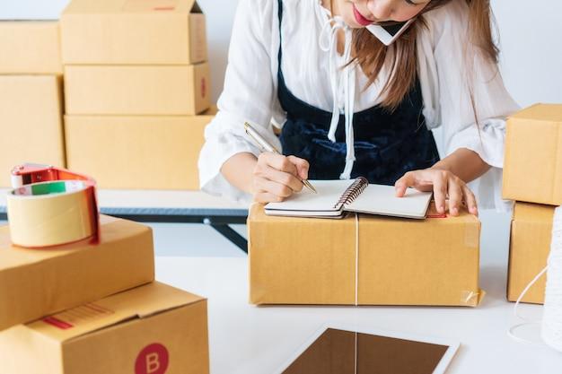 Vielbeschäftigter geschäftsinhaber, der mit dem kunden telefoniert, während er das notizbuch notiert