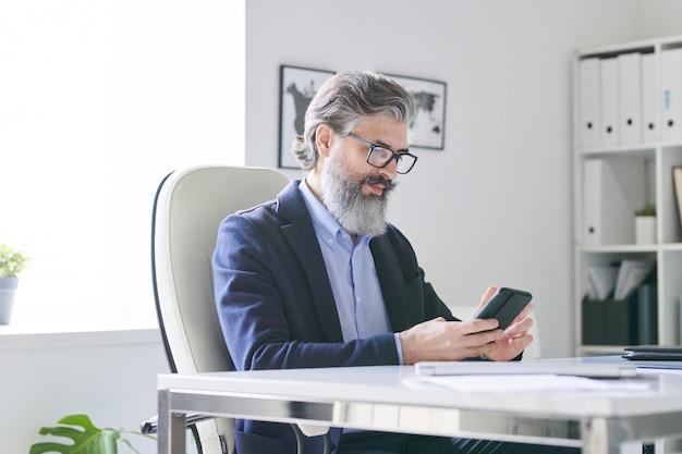 Vielbeschäftigter senior-profi mit grauem haar und bart, der im smartphone rollt, während er den zeitplan seiner kunden oder bewerber im büro überprüft
