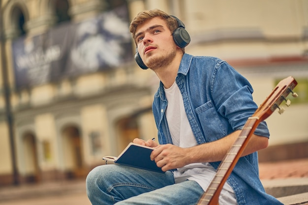 Vielbeschäftigter talentierter musiker schreibt ein neues lied in das notizbuch